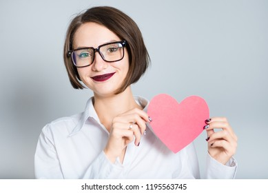 Portrait of a business woman holding a paper heart, love theme. short haircut in isolation over the background