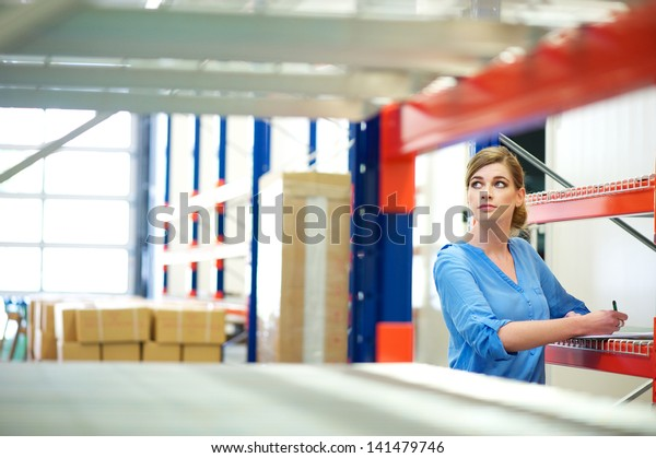 Portrait of a business woman inspector doing inventory in a warehouse