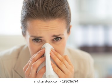 Portrait of business woman in office blowing nose