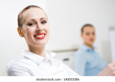 portrait of a business woman in office, smiling and looking into the camera, office work