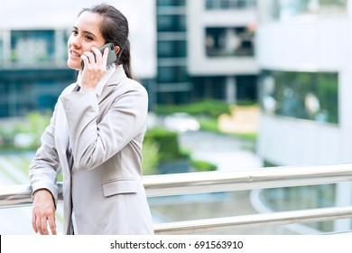 Portrait of business woman on phone. Young professional career business woman standing outside talking on mobile phone. Taken outdoor with natural light. For young woman leadership concept.