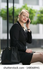 Portrait of a business woman sitting outdoors with cellphone
