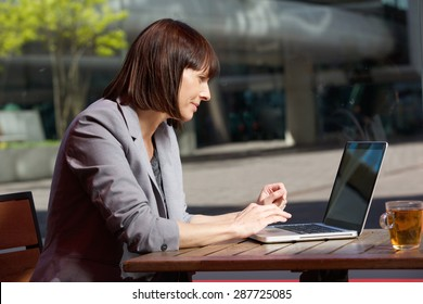Portrait of a business woman using laptop at cafe during break