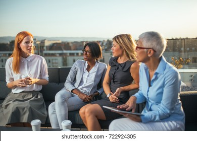 Portrait of business women having a pleasant outdoor meeting on the rooftop while drinking coffee.