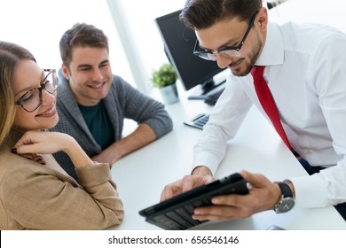 Portrait of business young man explaining terms of contract to his clients in the office.