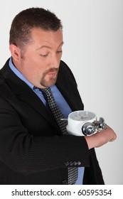 Portrait of a businessman with alarm clock