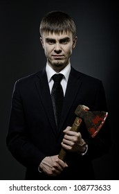 portrait  the   businessman  in black costume and black necktie with axe, sinister look