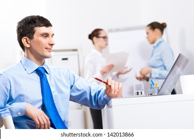 Portrait of a businessman in a blue shirt in the background of colleagues discussing