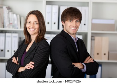 Portrait of businessman and businesswoman with arms crossed standing in office