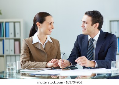 Portrait of businessman and businesswoman discussing plan or strategy at meeting