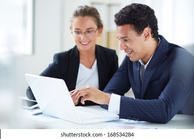 Portrait of businessman and businesswoman looking at laptop display at meeting