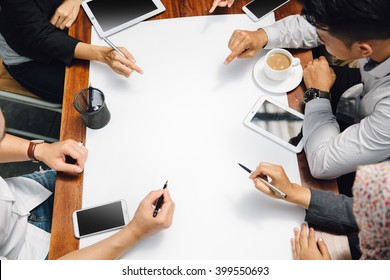portrait of businessman and businesswoman sitting in cafe meeting discussing something on paper. shoot from top view