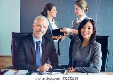 Portrait of businessman and businesswoman sitting in conference room
