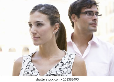 Portrait of a businessman and a businesswoman standing in the city and looking in different directions.