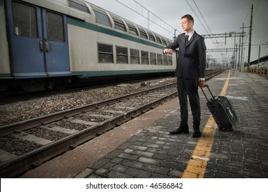 Portrait of a businessman carrying a suitcase and standing on the platform of a train station