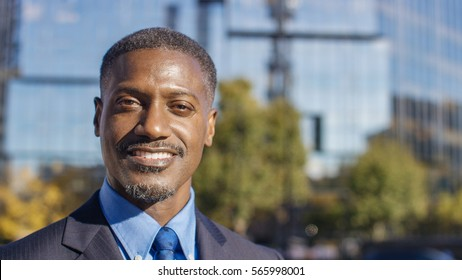 Portrait of businessman in the city smiling to camera