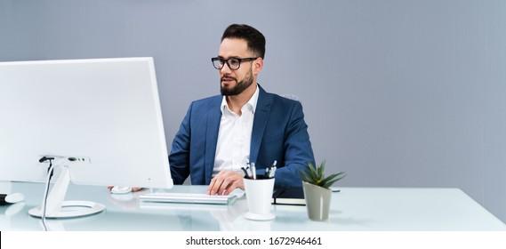 Portrait Of A Businessman At Desk Using Computer