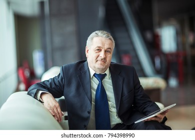 portrait of businessman with digital tablet sitting in the chair in front of the office.