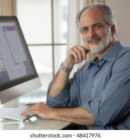Portrait of a businessman dressed in casual clothing and sitting in front of a computer. He is smiling at the camera with one hand on the keyboard and the other near his face. Square format.