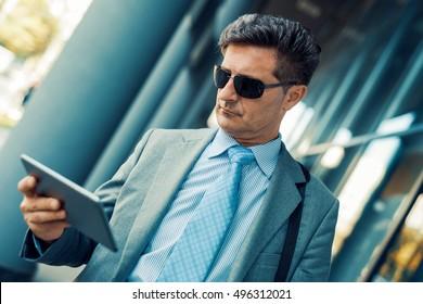 Portrait of  businessman dressed in suit work on digital tablet during break.
