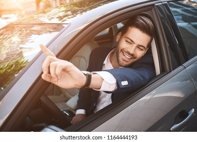 Portrait of businessman driving in car and smiling on his morning commute to work. Young man his finger pointing towards the camera.