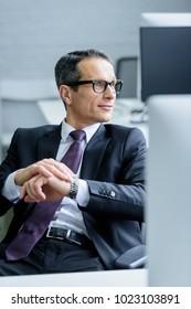 portrait of businessman in eyeglasses looking away in office