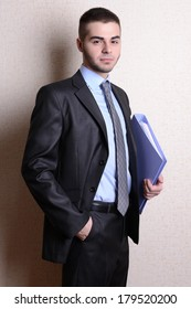 Portrait of businessman with folder near wall