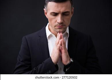 Portrait of a businessman in formal wear praying over black background