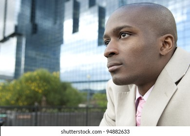 Portrait of a businessman in front of a modern office building in the city.