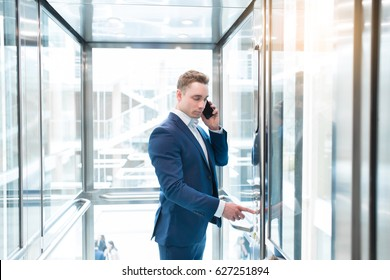 Portrait of businessman in glass office elevator talking on cell phone