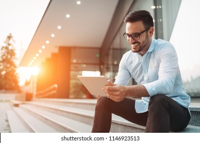 Portrait of businessman in glasses holding tablet