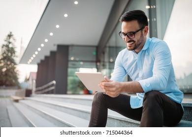 Portrait of businessman in glasses holding tablet