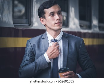 Portrait of a businessman grab the necktie and waiting for the subway train.