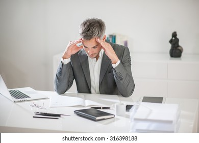 Portrait of a businessman with grey hair and beard having a hard time with some ideas. He is sitting at his white desk, holding his head in his hands above his notebook like if he was trying to think.