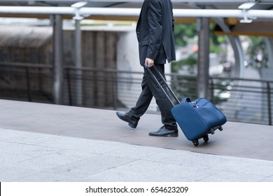 Portrait of a businessman with hand luggage walking through the metropolis city background.