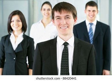 Portrait of a businessman and her colleagues at the background