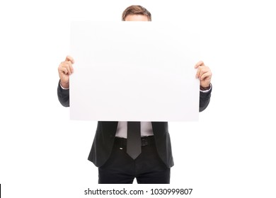Portrait of businessman holding blank sheet of paper on white background