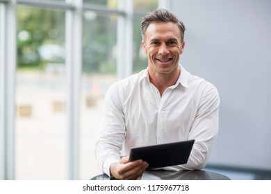 Portrait of a businessman holding digital tablet at conference centre