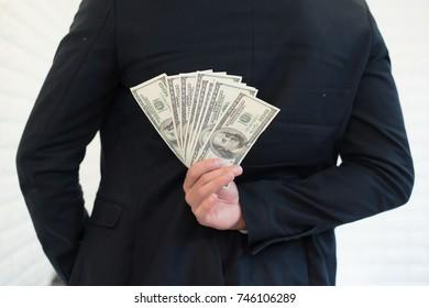 Portrait of a businessman holding money and hide it.