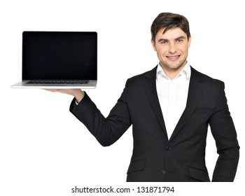 Portrait of  businessman holds on palm the opened  laptop with blank black screen isolated on white.