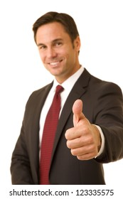 Portrait of a businessman isolated on white wearing a business suit and tie giving a thumbs up  selective focus on thumb