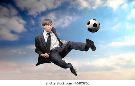 Portrait of a businessman kicking a ball