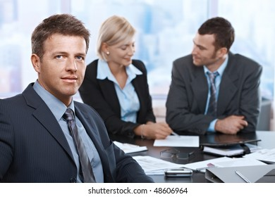 Portrait of businessman looking at camera sitting at meeting room with coworkers.