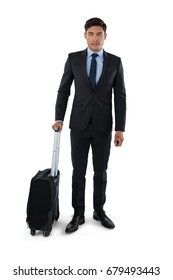 Portrait of businessman with luggage standing against white background