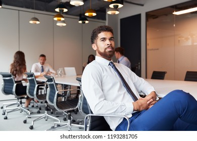 Portrait Of Businessman In Modern Boardroom With Colleagues Meeting Around Table In Background
