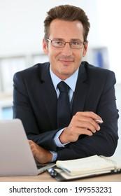 Portrait of businessman in office working on laptop