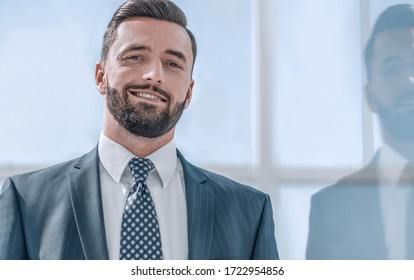 portrait of a businessman on the background of an office window