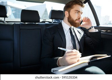 Portrait of a businessman with papers calling on smartphone and sitting on car back seat