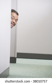 Portrait of a businessman peeking around a cubicle wall