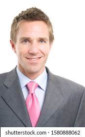 Portrait of businessman in pink tie and gray suit looking at the camera smiling against white background